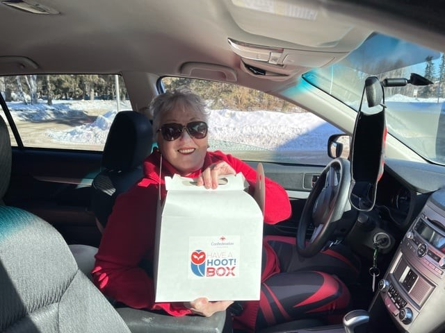 Woman sits in her car, smiling, holding a box with a Have a Hoot sticker on it.